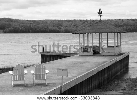 A black and white image of an old weathered private empty dock on Lake Michigan with two chairs and gazebo showing a peaceful scene overlooking the water.
