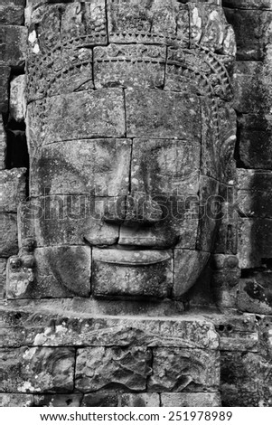 a black and white image of ancient faces carved in stone now part of ruins located in Cambodia - stock photo