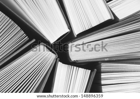 A black and white image of hardback books or text books from above. Books and reading are essential for self improvement, gaining knowledge and success in our careers, business and personal lives - stock photo