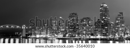 A black and white panorama, with an aspect ratio of 3:1, of False Creek in Vancouver at nighttime, in British Columbia, Canada. - stock photo