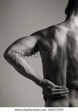 A black and white photo of a muscular man holding his lower back as if experiencing a backache. - stock photo