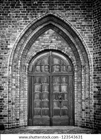 A black and white photo of an arched doorway to a gothic style church. - stock photo