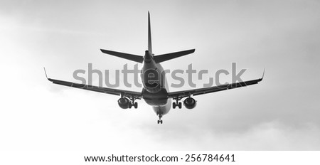A black and white photograph of a commercial jet preparing for landing. - stock photo