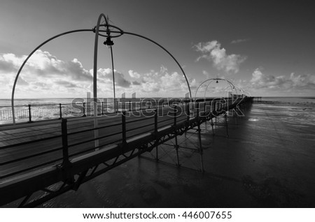 a black and white photograph of a pier
