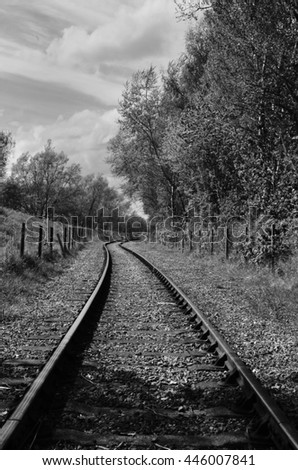 A black and white photograph of a railway track  - stock photo