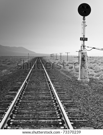 A black and white photograph of an old fashioned railroad light and railroad. - stock photo