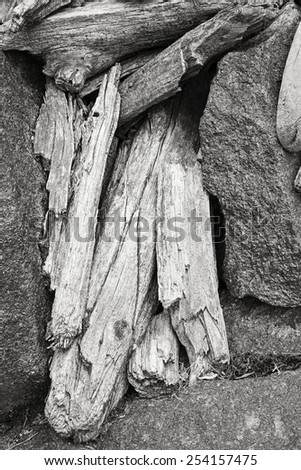 A black and white photograph of piled driftwood, isolated in between rocks in Yosemite National Park. - stock photo