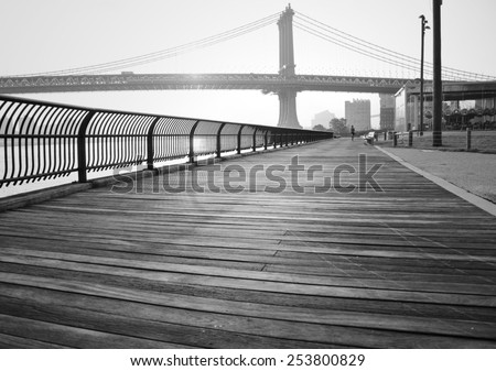 A black and white photograph of the Manhattan Bridge, taken from a wooden walking path in Brooklyn Bridge Park. - stock photo