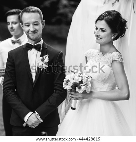 A black and white picture of merry newlyweds during the ceremony