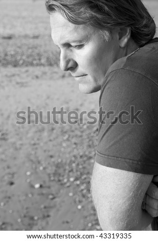 A black and white portrait photo of a depressed and lonely looking mature man in his forties - stock photo