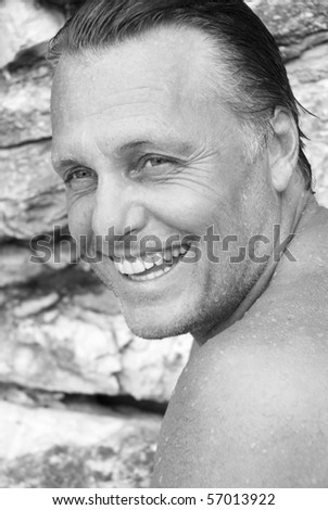 A black and white portrait photo of a happy smiling man in his forties with his wet hair slicked back. - stock photo