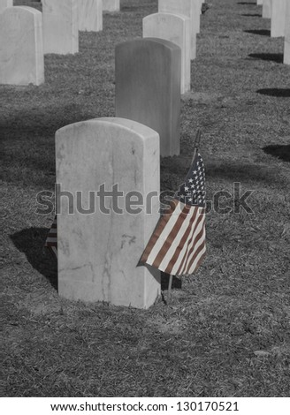 A black and white - selective color of gravestones and flag in a National Cemetery. - stock photo