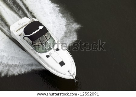 A black and white speedboat shot from above while traveling fast. - stock photo