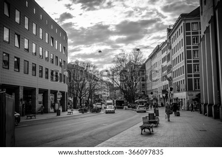 A black and white view of a commercial street in downtown Munich, Germany