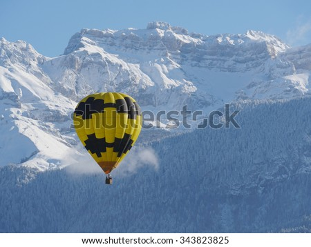 a black and yellow hot air balloon with the snowy mountain at the back - stock photo