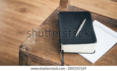 A black Bible with a pen rests over an open paper notebook on an old wooden chair. - stock photo
