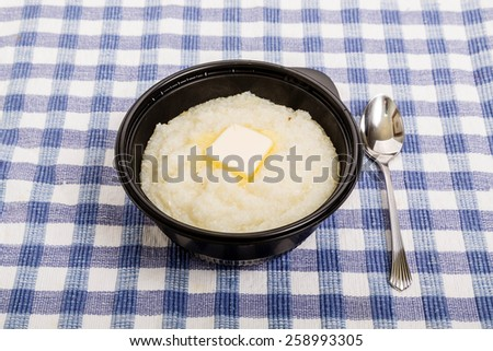 A black bowl with white corn grits and melting butter on a blue plaid cloth - stock photo