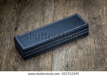 a black box on wood background. black case box, leather box, leather boxes, PU box