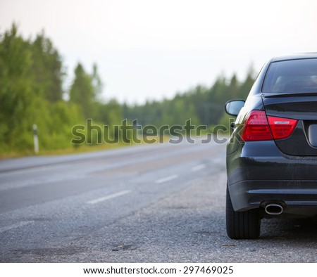 A black car is parked in the side of the road in the summer on a asphalt road. - stock photo