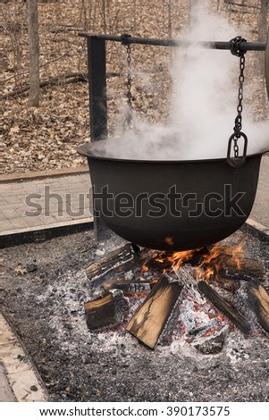 A black cauldron suspended with chain over a burning wood fire emits steam from the boiling of liquid as the water evaporates, in this case boiling maple sap in the producing of maple syrup - stock photo