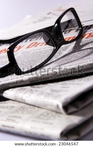 A black frame eyeglasses on a stack of newspaper. - stock photo