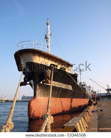 A black freight ship is tied up in port - stock photo