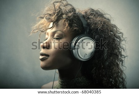 A black girl is listening to the music
