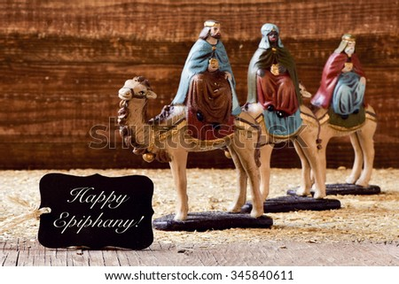 a black label with the text happy epiphany and the three kings on their camels - stock photo