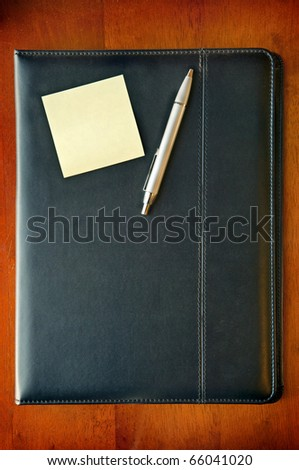 A black leather executive folder on timber desk with sticky note and silver pen - stock photo