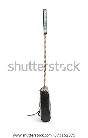 A black leather hand bag with iron decoration, string on the bottom isolated white.
