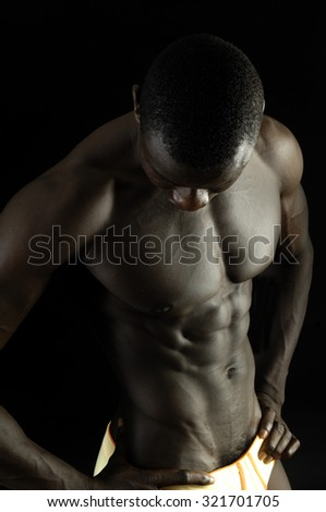A black man with a muscular body, black background.