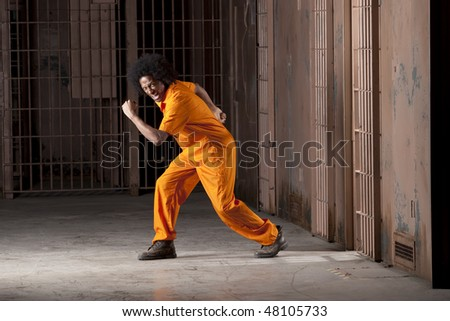 A black man with an afro making various faces and gestures inside a federal prison - stock photo