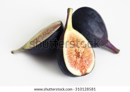 A black mission fig sliced in half to show the inside of the fruit.  The halves are propped up against a whole, uncut fig to show the exterior of the fruit. - stock photo