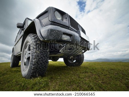 A black offroad all terrain vehicle on a green pasture in the mountains - stock photo