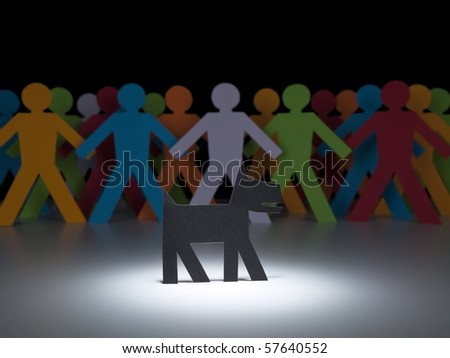 A black paper dog stands under the spotlight in front of a multicolor crew. - stock photo