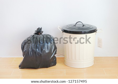 a black plastic bag and reuse disposal bin - stock photo