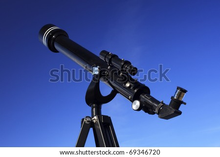 A black refracting telescope pointed towards blue sky. - stock photo