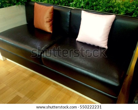 A black sofa with Brown and white cushion
