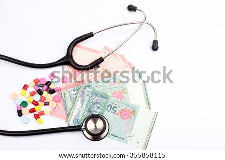 a black stethoscope and colorful pills on various Malaysian currency - stock photo
