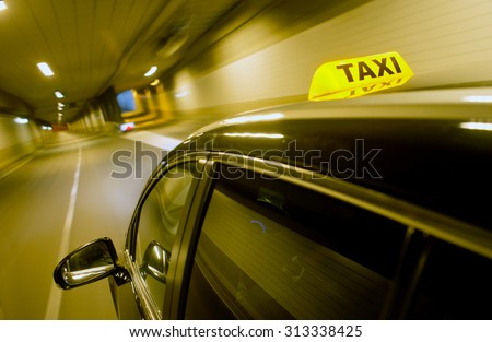 A black taxi, driving through a dunnel, with the taxi sign lit, apporaching a junction and exit ramp - stock photo
