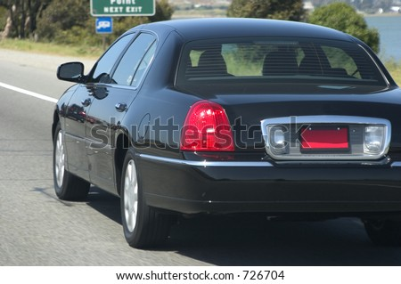 A black town car speeds along the highway. - stock photo