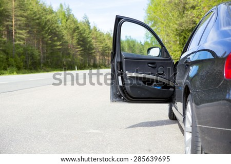 A black vehicle with an open door in side of the road. Image taken during summer. The driver is needing for help or giving assistance for example. - stock photo