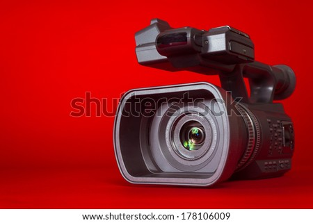 A black video camera on a red background with copy space - stock photo