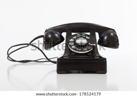 A black, vintage rotary phone on a white background - stock photo