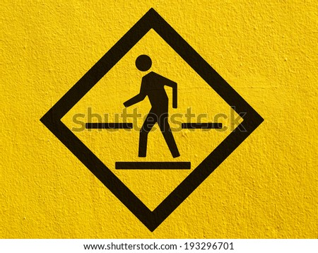 a black walking across the street painted on a stucco wall outside - stock photo