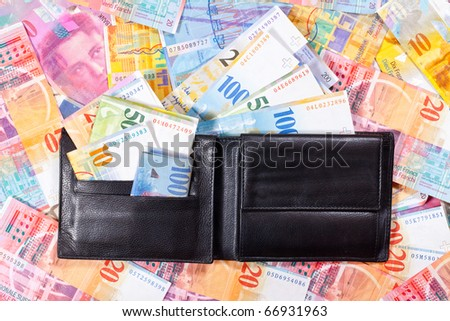 A black Wallet with Swiss Francs, is lying on a Table full of Swiss Francs - stock photo