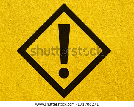 a black warning attention sign points painted on a stucco wall outside - stock photo