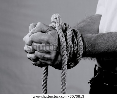 A black & white picture from a man's tied hands - stock photo