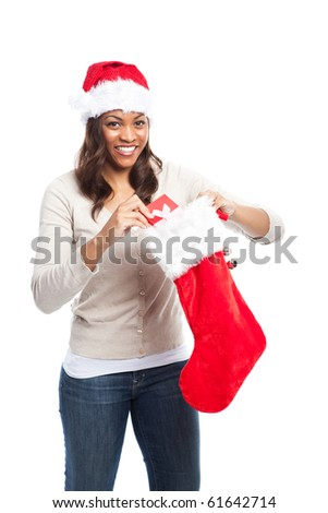 A black woman celebrating christmas picking out gift from stocking - stock photo