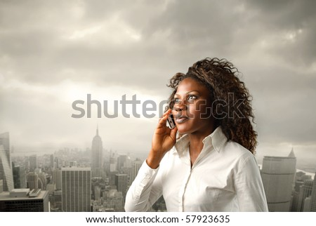 A black woman is listening at a mobile phone on a city background